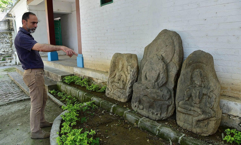 اطالوی ماہر آثار قدیمہ پتھروں پر تراشے گئے مجسموں کے بارے میں بتا رہے ہیں—فوٹو: اے ایف پی