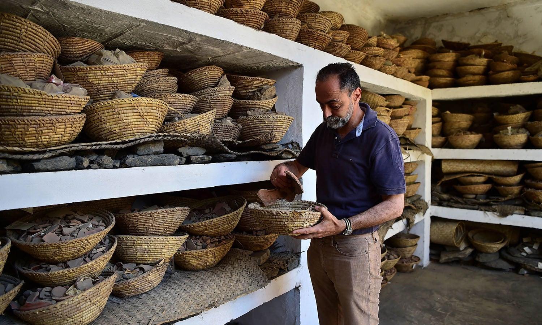 ماہر آثار قدیمہ تاریخی مقام سے جمع کیے گئے ٹکڑوں کو حفاظت سے رکھ رہے ہیں—فوٹو:اے ایف پی