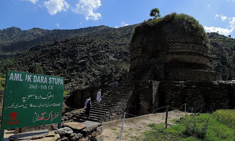 سوات میں تاریخی مقام کی نشاندہی کرنے والا بورڈ آویزاں ہے، پس منظر میں بدھ اسٹوپا بھی موجود ہے—فوٹو: اے ایف پی