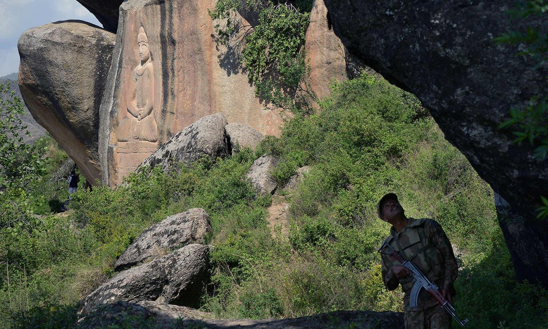 سوات میں موجود آثار قدیمہ کی حفاظت کے لیے سیکیورٹی اہلکار چاک و چوبند کھڑا ہے—فوٹو: اے ایف پی