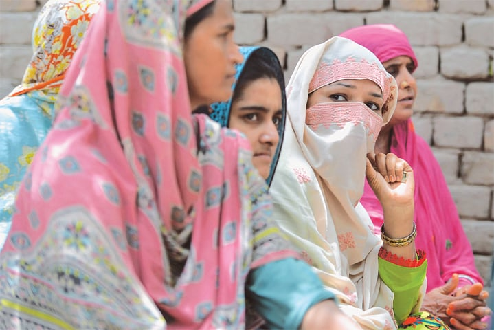Women who never voted in past general elections listen to a social worker and member of district council Bismillah Noor (not in the photo) trying to convince them to vote in upcoming polls in Mohripur.—AFP