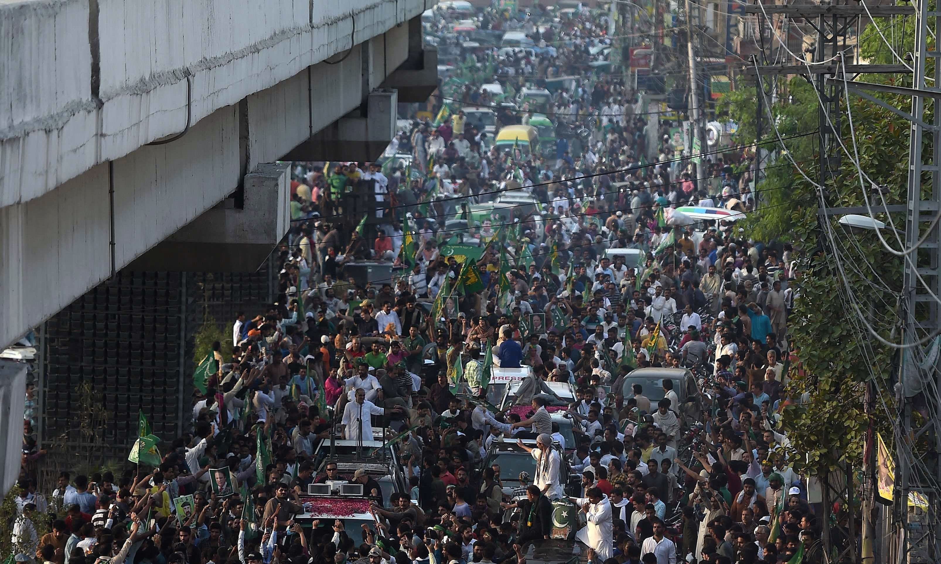 PML-N supporters take part in a march towards the airport ahead of the arrival of Nawaz Sharif in Lahore. — AFP