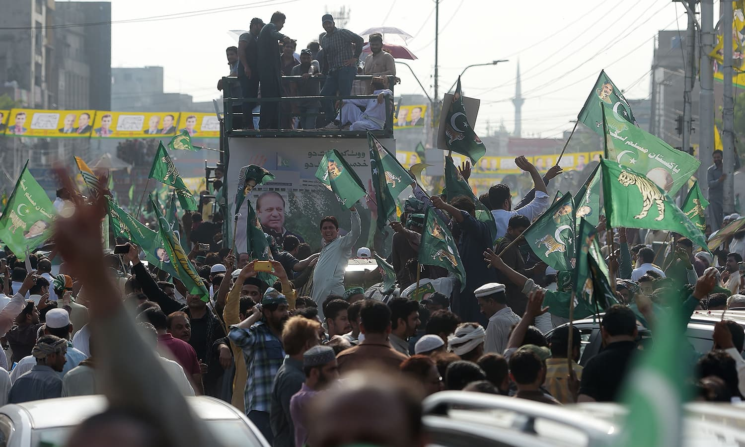 Supporters of Nawaz Sharif take part in a march towards the airport ahead of his arrival. —AFP