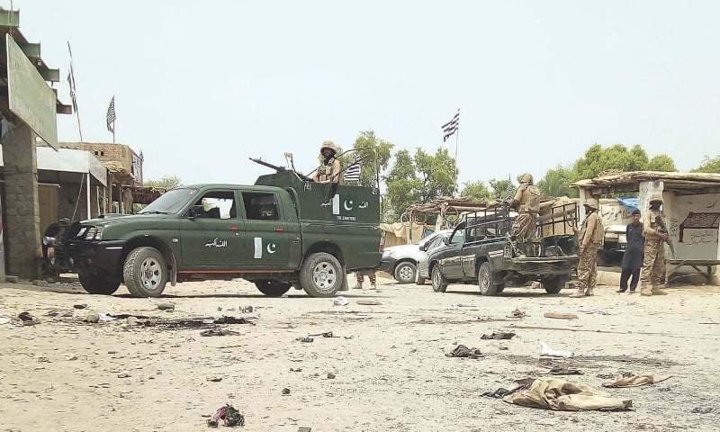 PAKISTAN Army troops guard the area of suicide attack at an election rally in Bannu on Friday.—AP