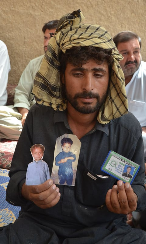 A man holds up pictures of his children who were victims of the Mastung blast. — Photo courtesy: Hafeezulah Sheerani