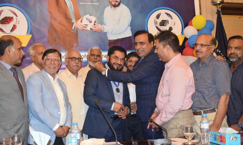 SIALKOT: SCCI President Zahid Latif Malik awards a gold medal to Khawaja Masud Akhtar on Saturday.