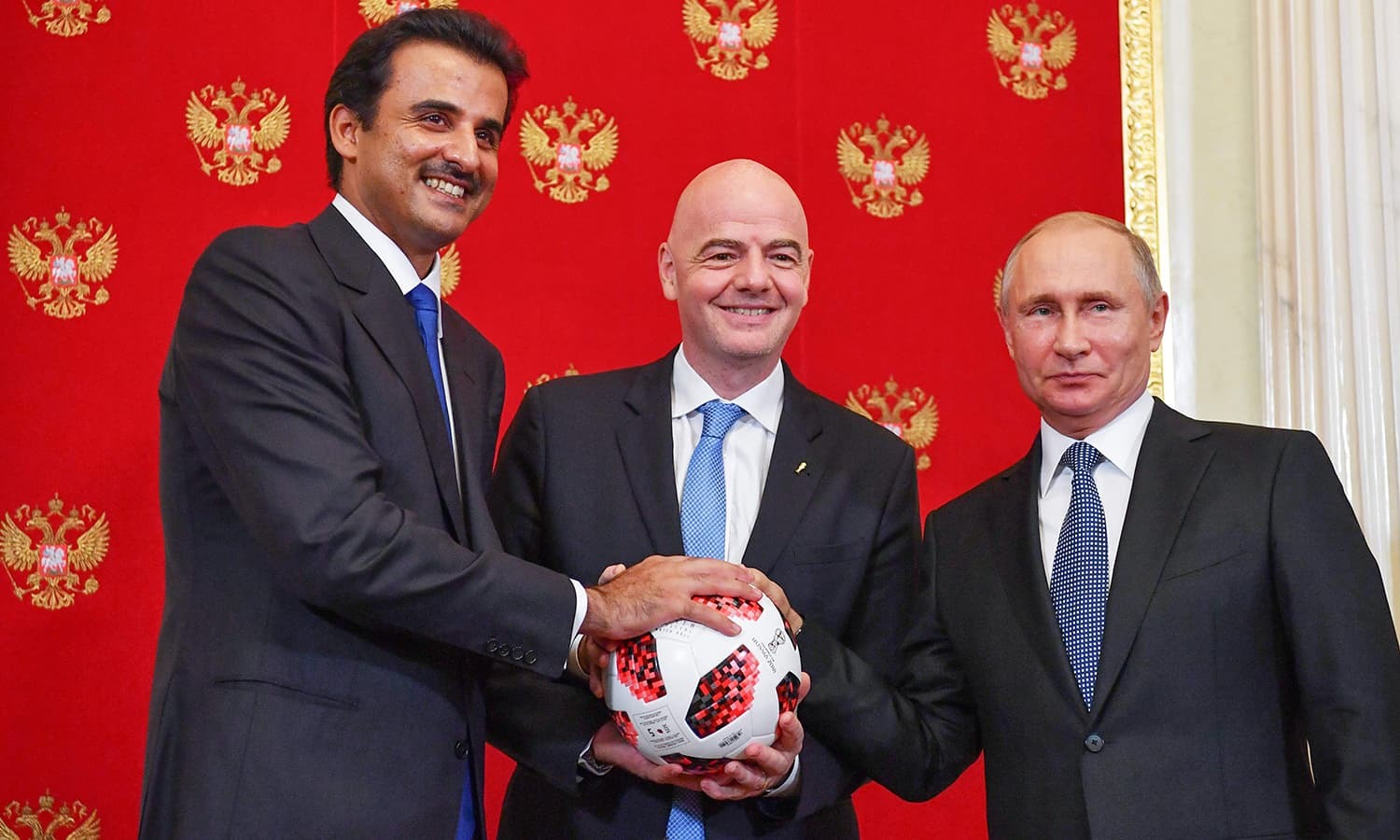 (From L) Emir of Qatar Sheikh Tamim bin Hamad Al-Thani, FIFA President Gianni Infantino and Russian President Vladimir Putin pose for a photograph during a symbolic transfer of the authority to Qatar to host the World Cup 2022 at the Kremlin in Moscow. — AFP