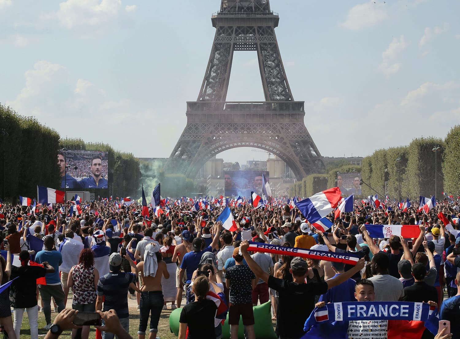 People gather on the fan zone in front of the Eiffel Tower to watch the Russia 2018 World Cup final football match between France and Croatia, on the Champ de Mars in Paris. — AFP