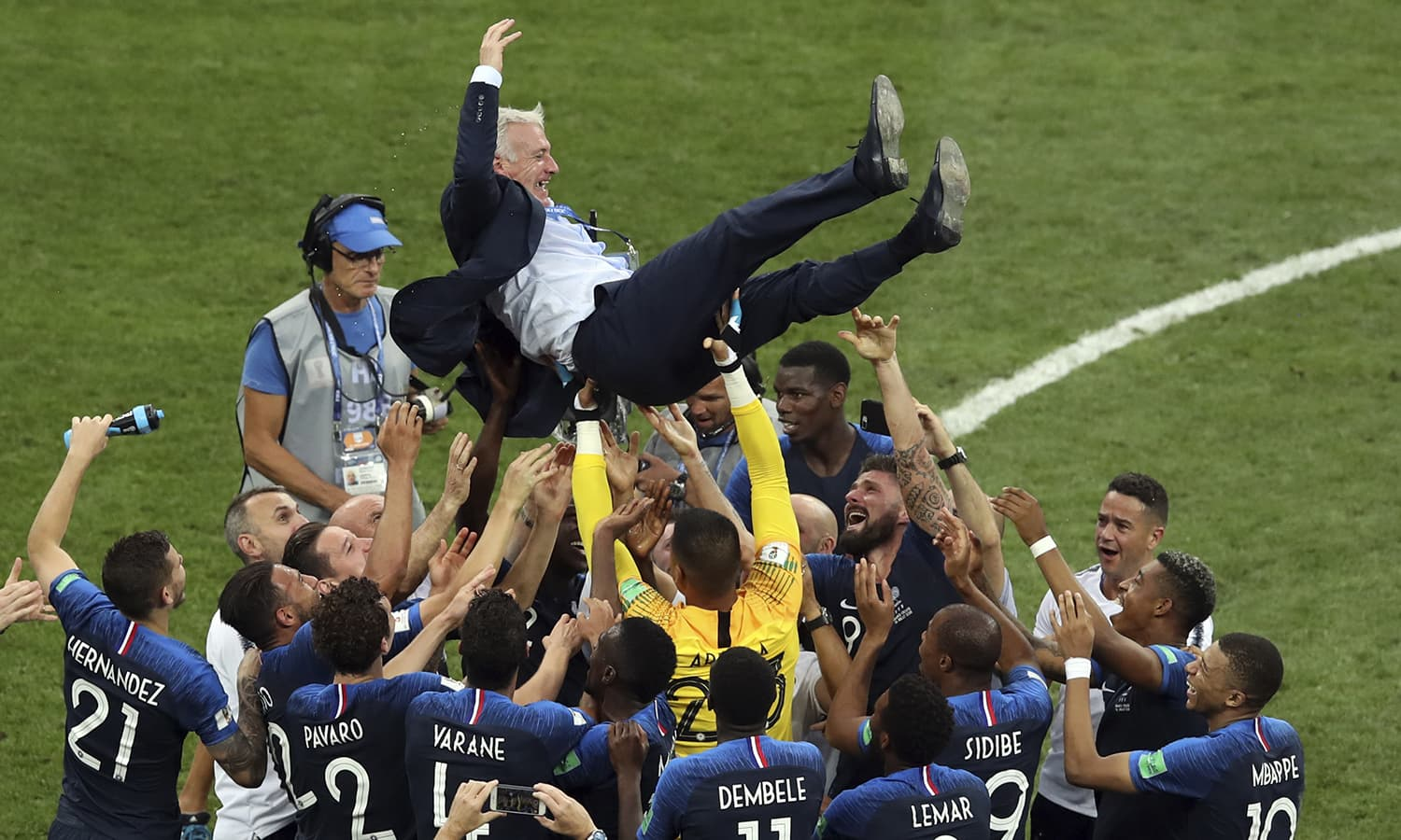 French players throw France head coach Didier Deschamps into the air celebrating at the end of the final match between France and Croatia. — AP
