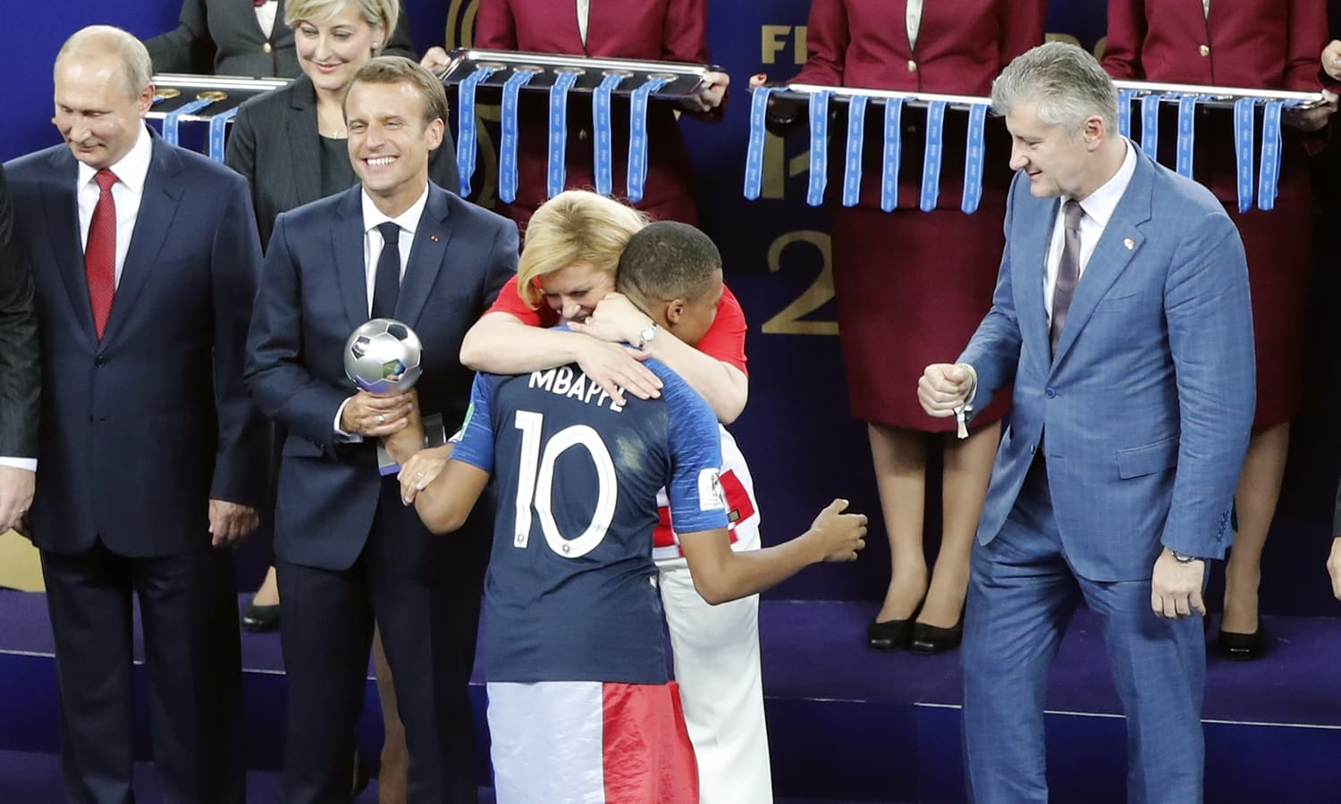 Croatian President Kolinda Grabar-Kitarovic embraces France's Kylian Mbappe after he received the player of the tournament award. — AP