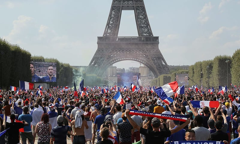People gather on the fan zone in front of the Eiffel Tower to watch the Russia 2018 World Cup final — AFP