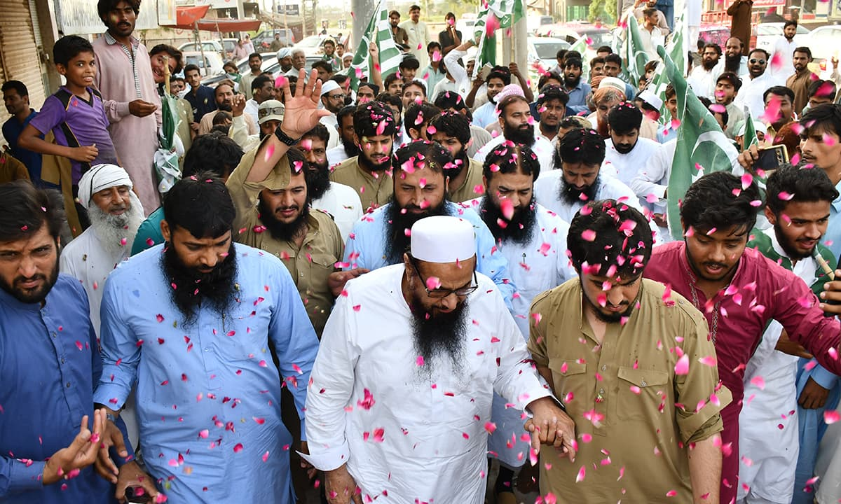 Hafiz Saeed is showered with rose petals as he arrives in Faisalabad for the election campaign | Rizwan Safdar