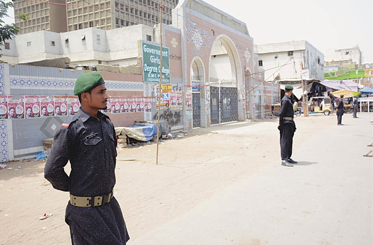 SECURITY men stand guard outside a polling station in Liaquatabad on Monday.—PPI