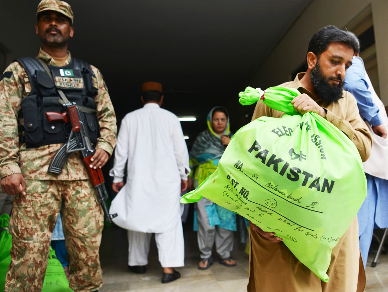 A soldier stands guard as an election official carries election materials at a distribution centre in Islamabad. ─AFP