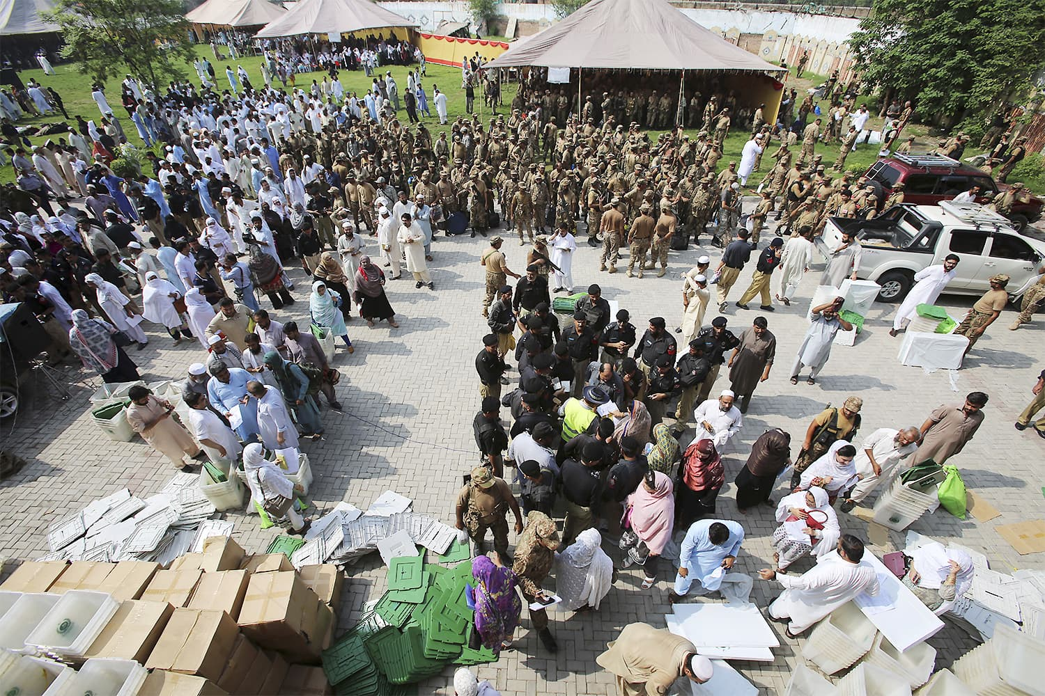 Election staff gather at a distribution centre to receive polling material for elections in Peshawar on Tuesday. ─ AP