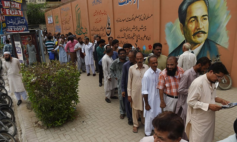 Election officials wait outside a distribution centre to collect ballot boxes and voting materials in Karachi. — AFP