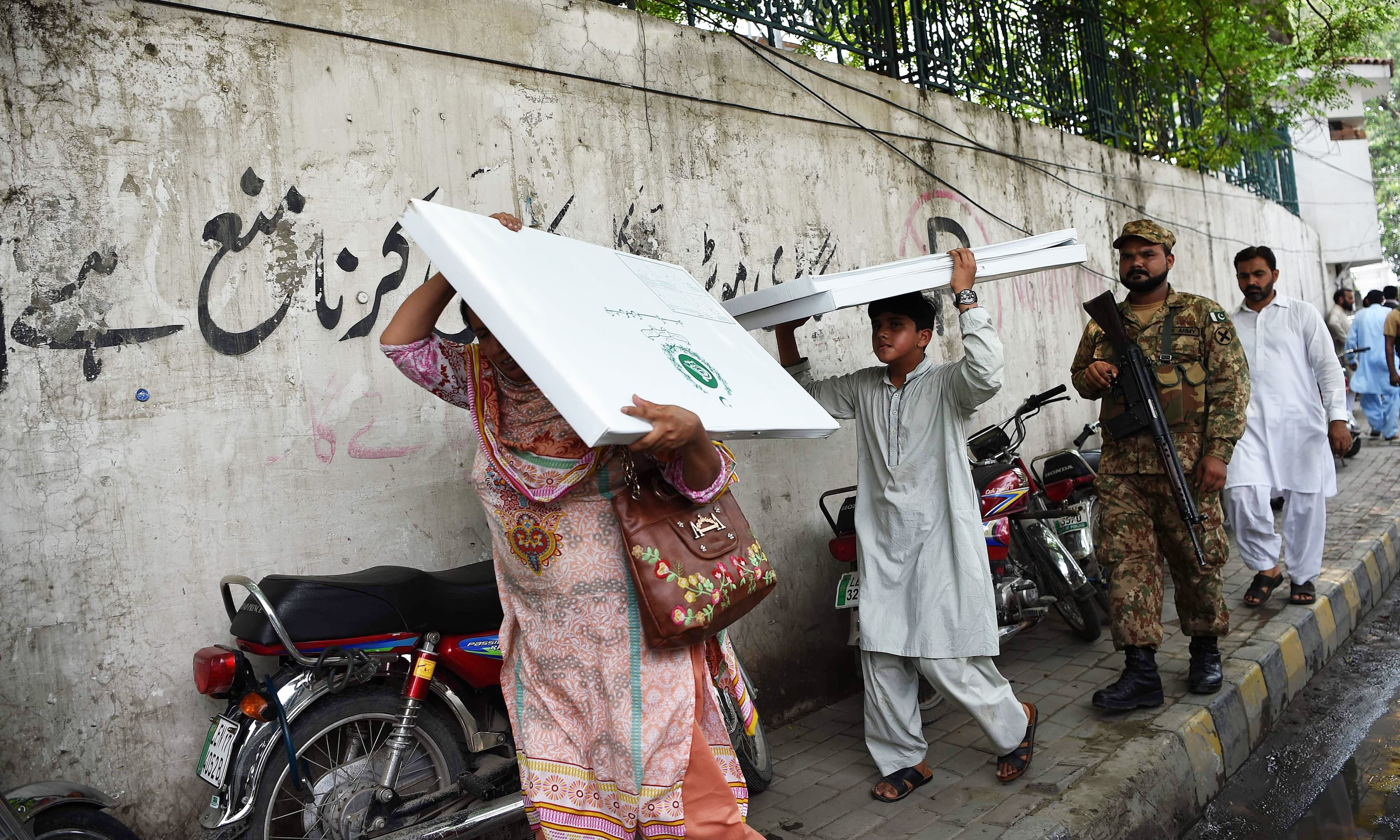 Polling official carries election material as a soldier escorts her in Lahore. —AFP