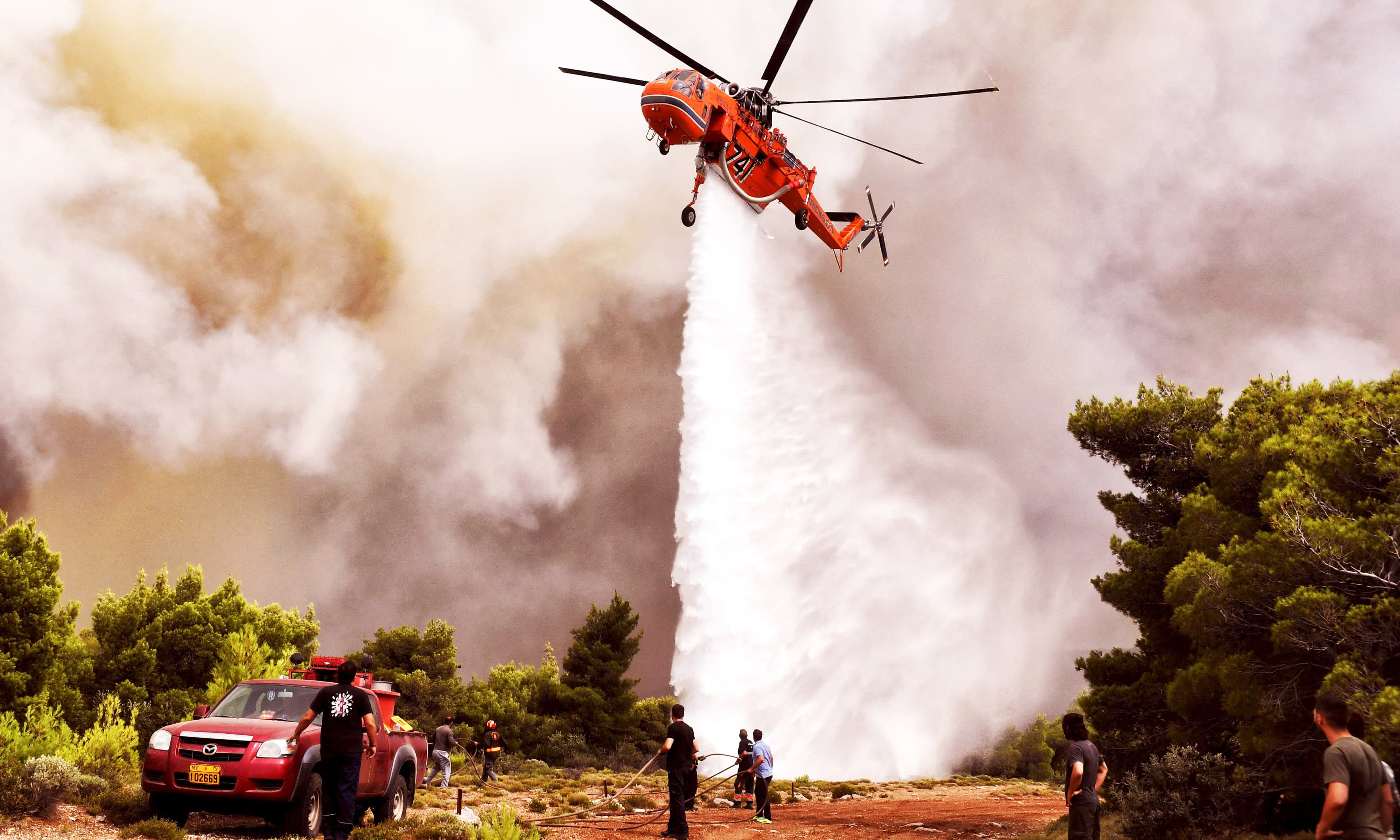 A helicopter drops water to extinguish flames. —AFP