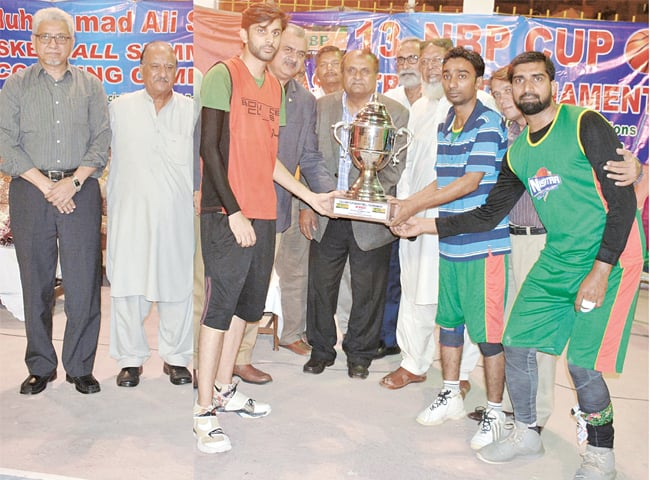KARACHI: NBP's sports head and former Test spinner Iqbal Qasim hands winners trophy to Bounce Club captain Muzammil Hussain at Arambagh court on Monday.
