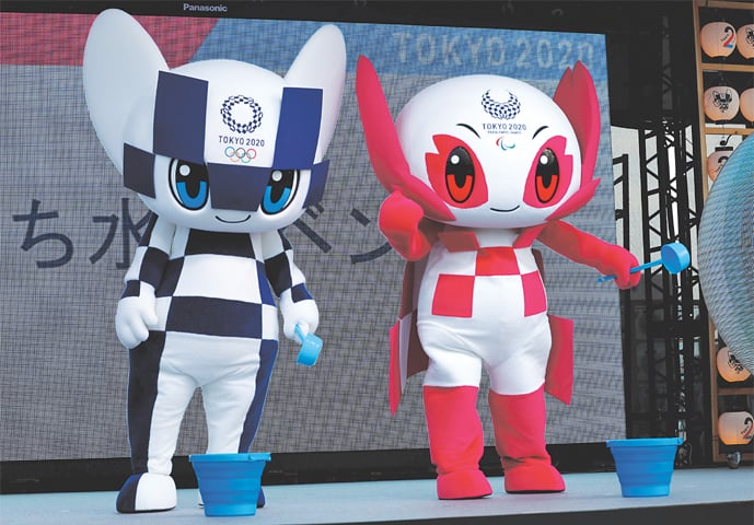 2020 Olympic Games mascot Miraitowa and Paralympic mascot Someity holds ladle to splash water during an old Japanese tradition called Uchimizu ritual on Tuesday prior to a countdown event to mark the two years until the Tokyo Olympics.—Reuters