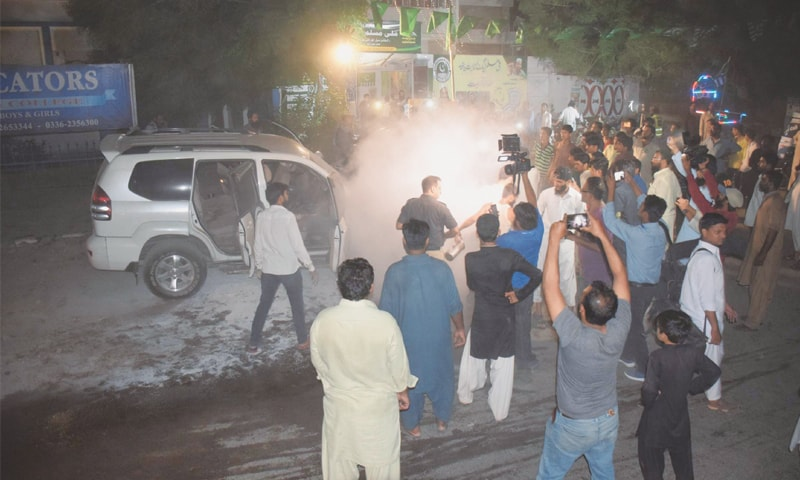 SMOKE billows from the car after it was hit by a cracker in Latifabad on Tuesday.—Dawn