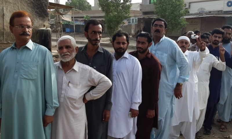 People line up outside a polling station in Sanghar. — DawnNewsTV