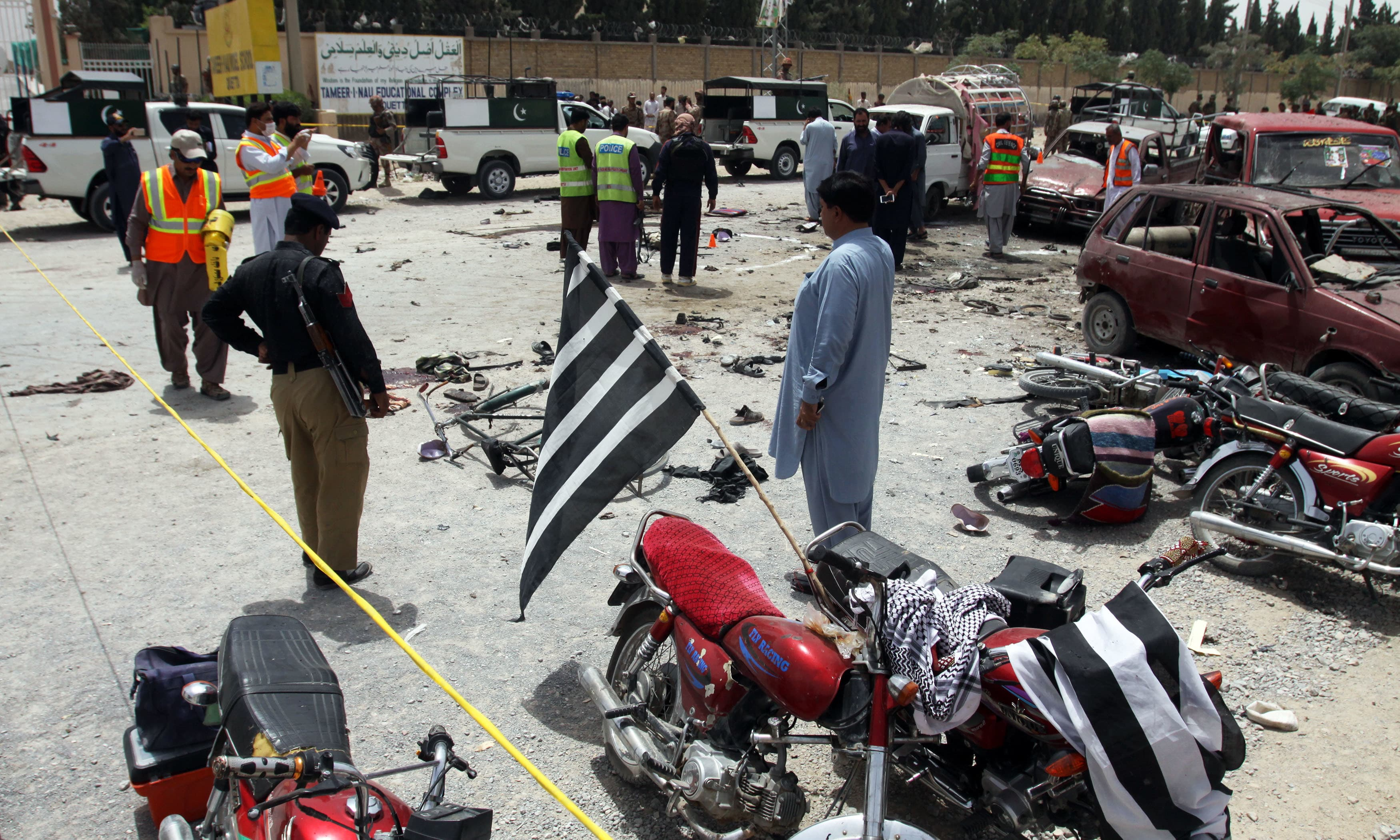 Volunteers and security officers visit the site of a bombing in Quetta. —AP