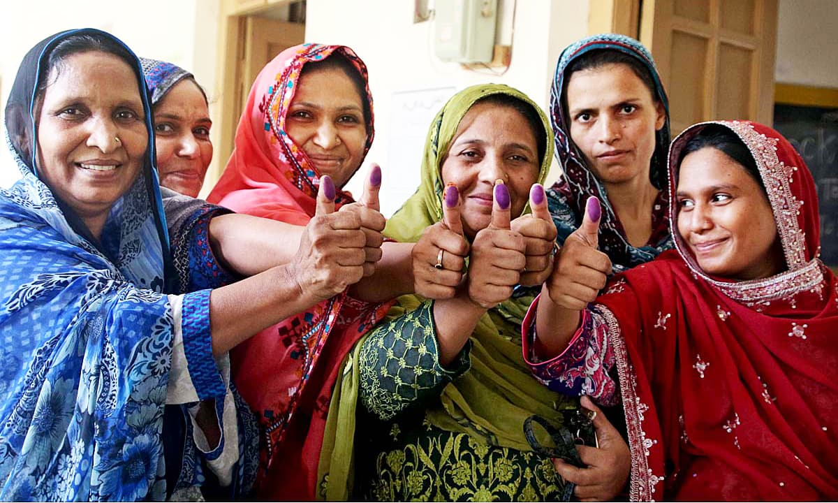 Women voters display their marked thumbs after casting their ballots in Qasimabad. —APP