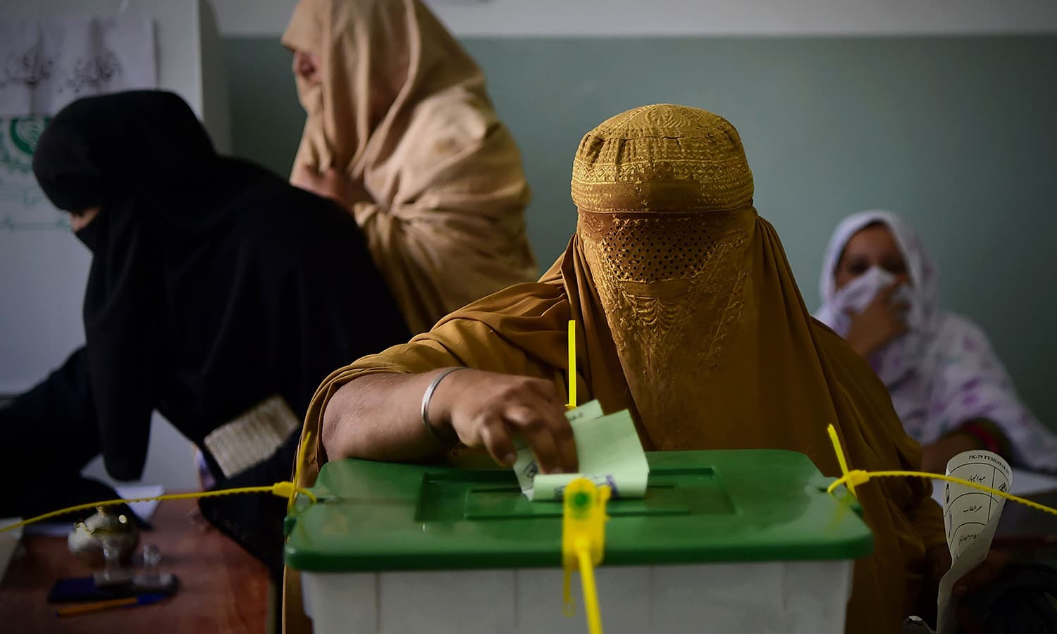 A woman casts her vote at a polling station in Peshawar. — AFP
