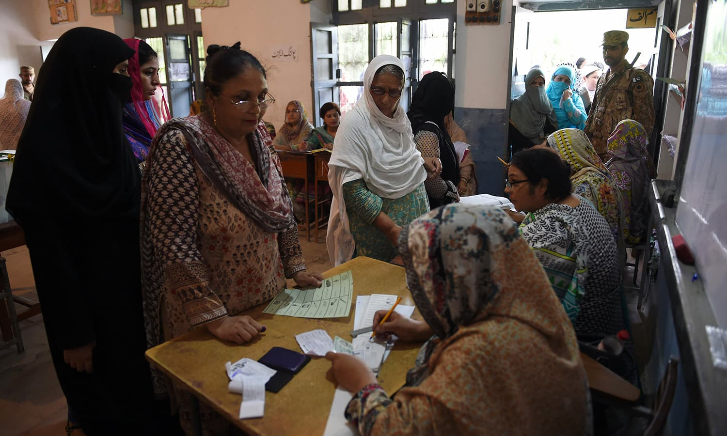 Voters line up to cast their ballot at a polling station in Rawalpindi. — AFP