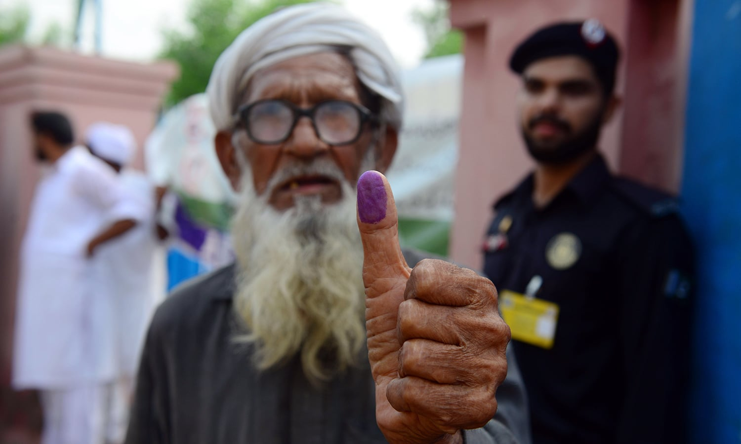 An elderly man shows his inked thump after casting his vote outside a polling station in Lahore. — AFP