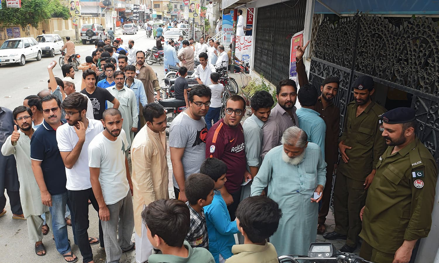Voters lineup to cast their ballot outside a polling station in Rawalpindi. — AFP
