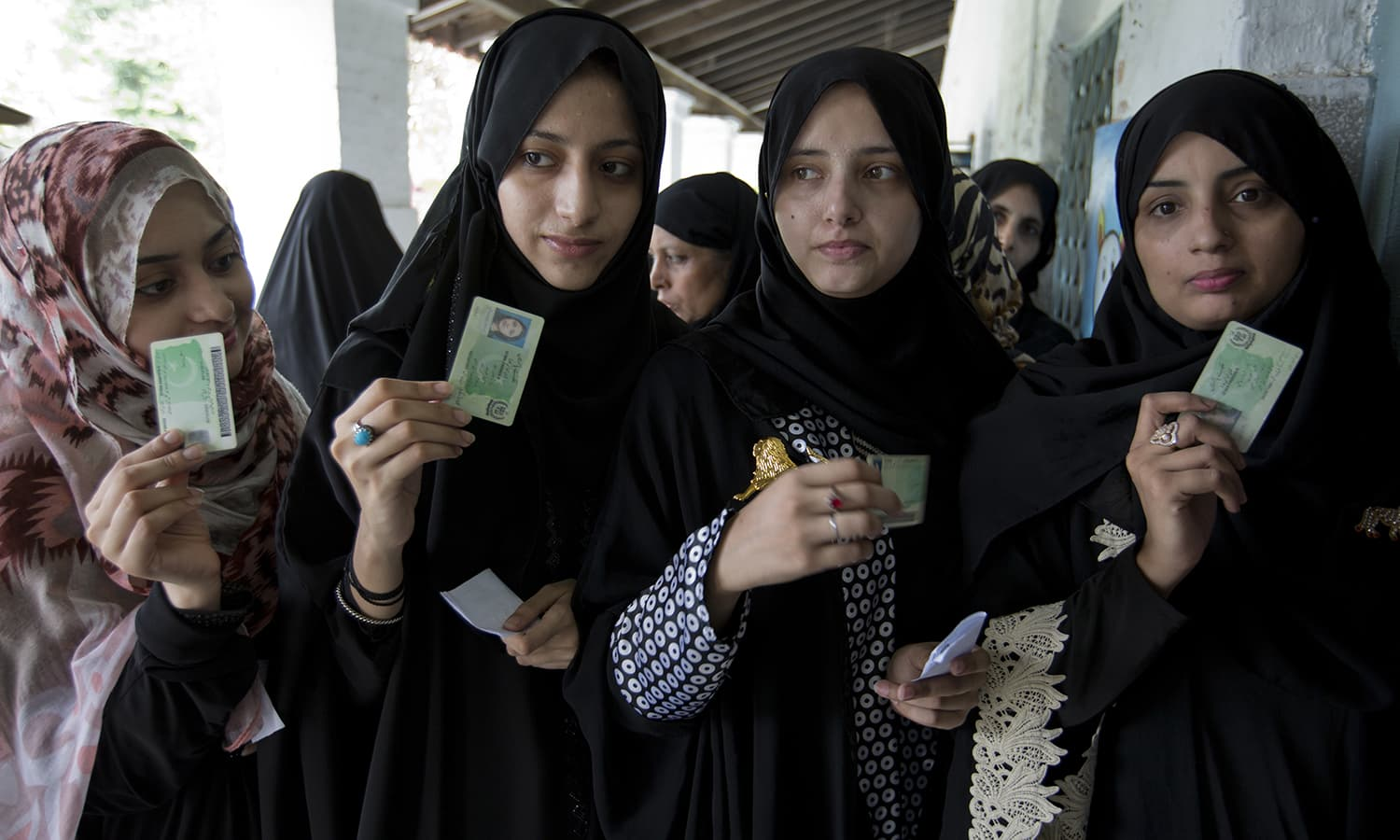 Women voters pose with their identity cards waiting to cast their vote in Rawalpindi. — AP