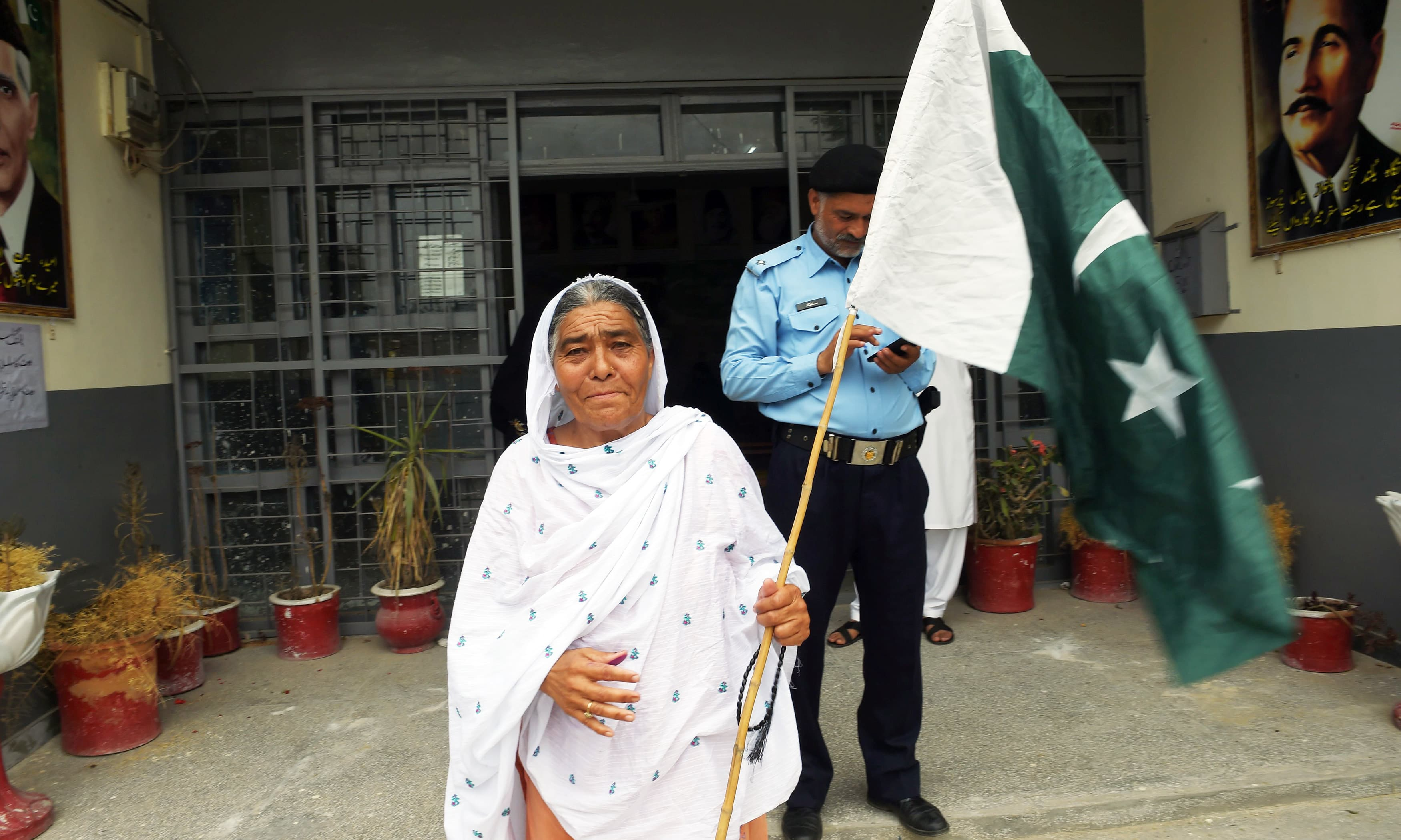 A woman walks out of a polling station holding flag after casting her ballot in Rawalpindi. —AFP