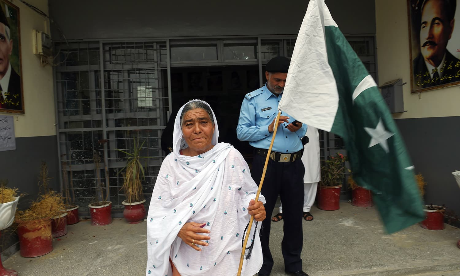 A woman walks out of a polling station holding Pakistan's national flag after casting her ballot in Rawalpindi. — AFP