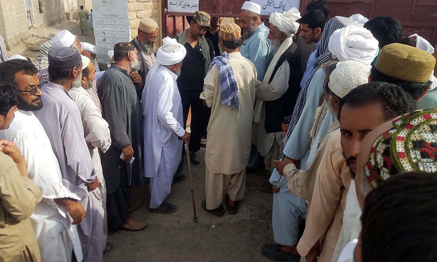 Voters stand in a queue outside a polling station in Balochistan's Dalbandin area to cast their ballots. — APP