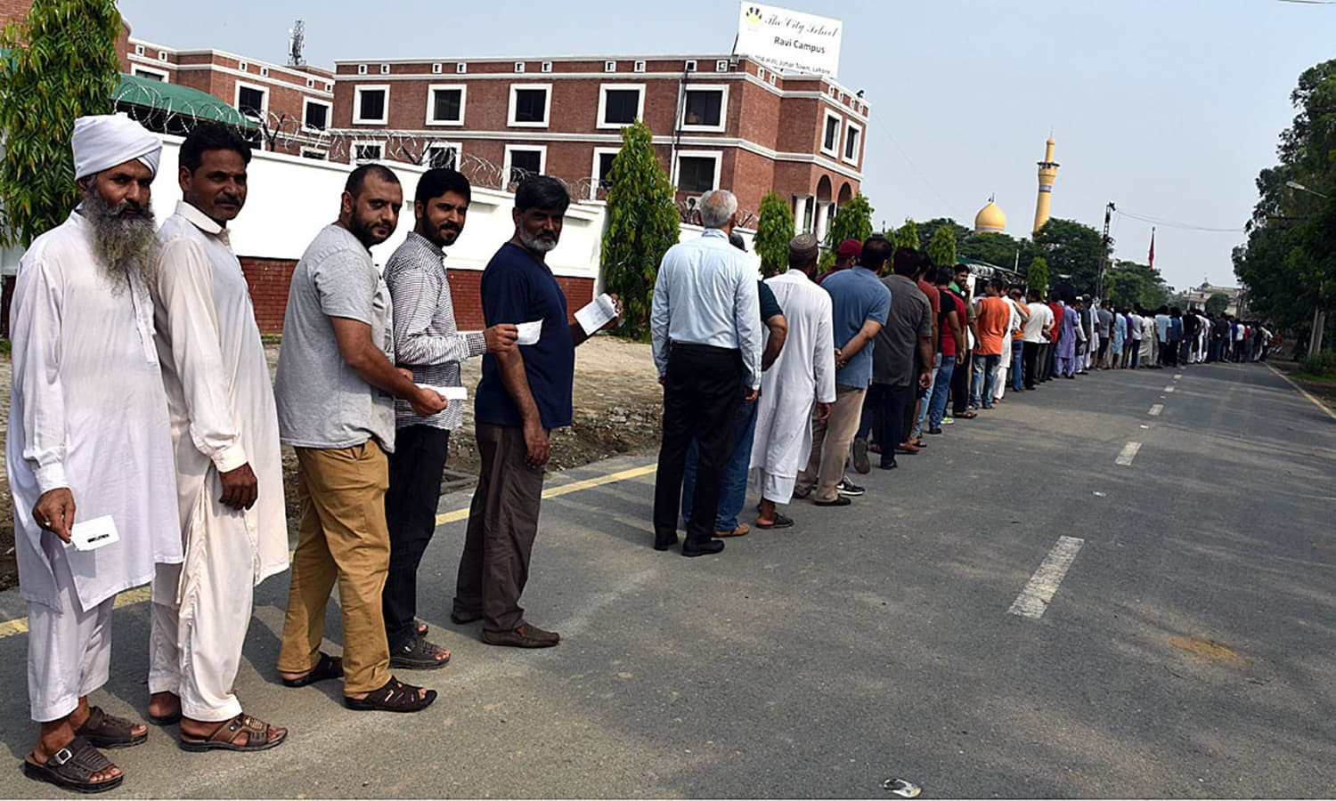 Voters stand in a queue to cast their ballots outside a polling station for NA-135 and PP-161 constituencies at City School, Johar Town in Lahore. — APP
