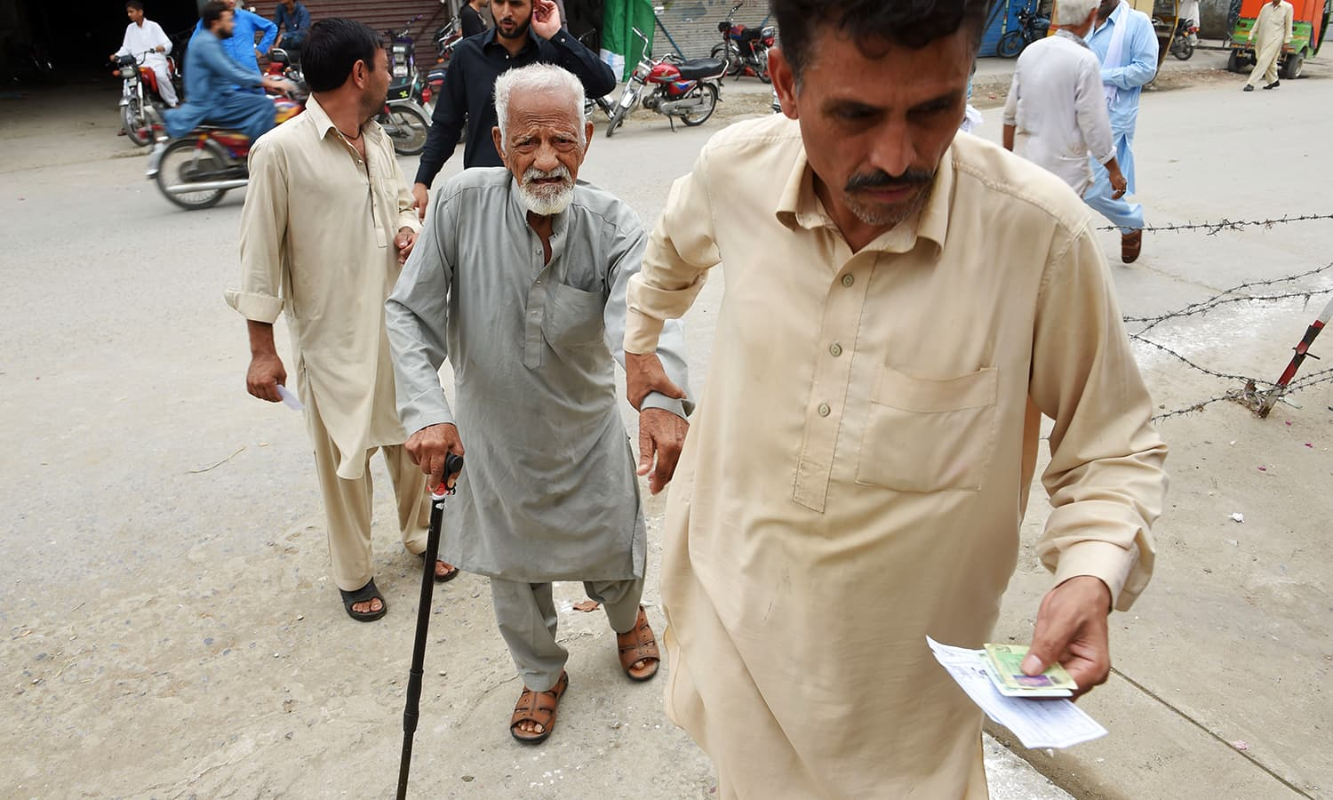 An elderly man is assisted by his son as they arrive at a polling station in Rawalpindi. — AFP
