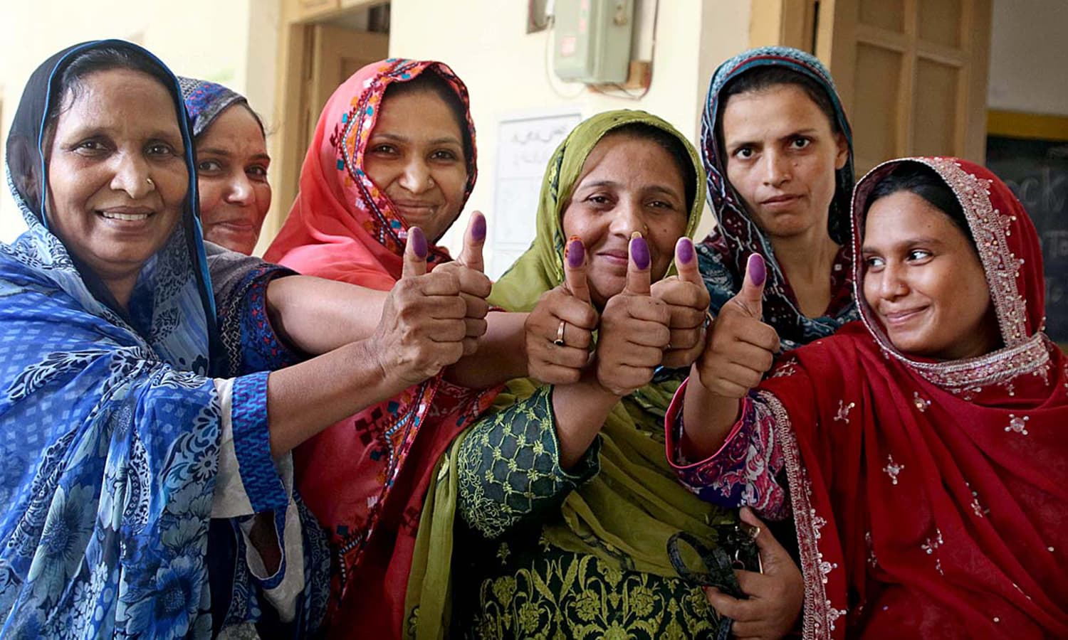 Voters displaying their marked thumbs after casting their ballots at a polling station in Qasimabad, Hyderabad. — APP