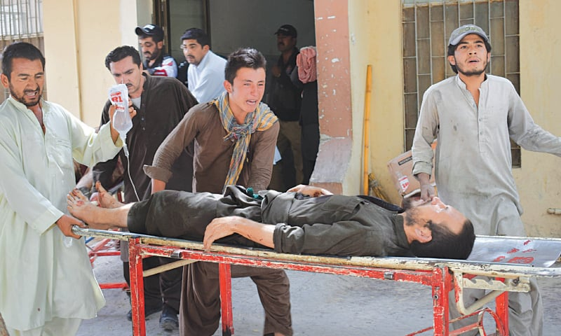 A RELATIVE weeps (centre) as he pushes an injured blast victim on a stretcher at a hospital after the suicide attack.—AFP
