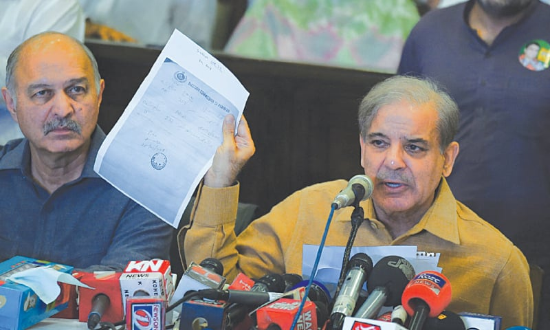 PML-N president Shahbaz Sharif shows a document as he speaks during a press conference at his office in Lahore on Wednesday.—AFP