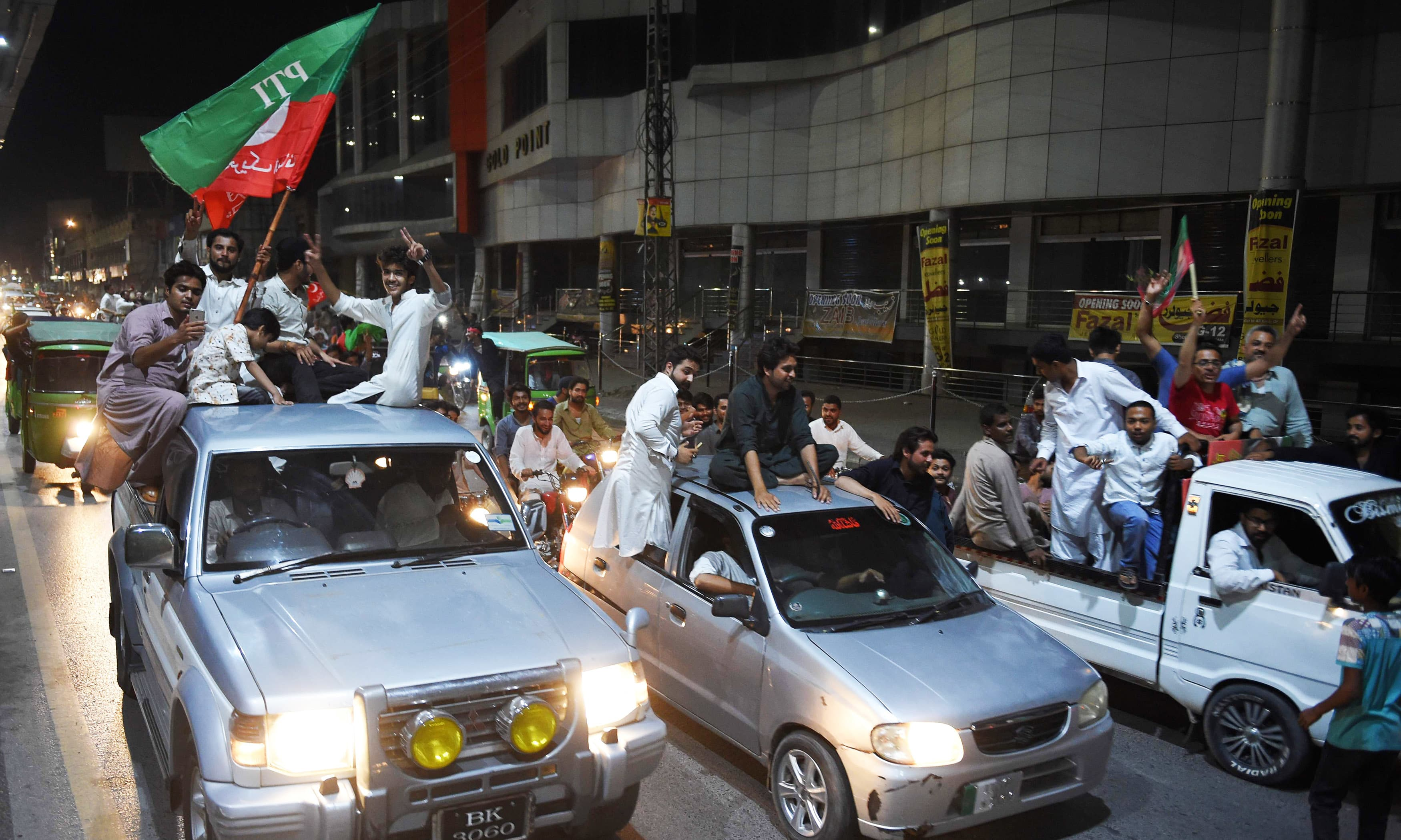 PTI supporters ride on vehicles in a convoy as they celebrate in Rawalpindi. —AFP