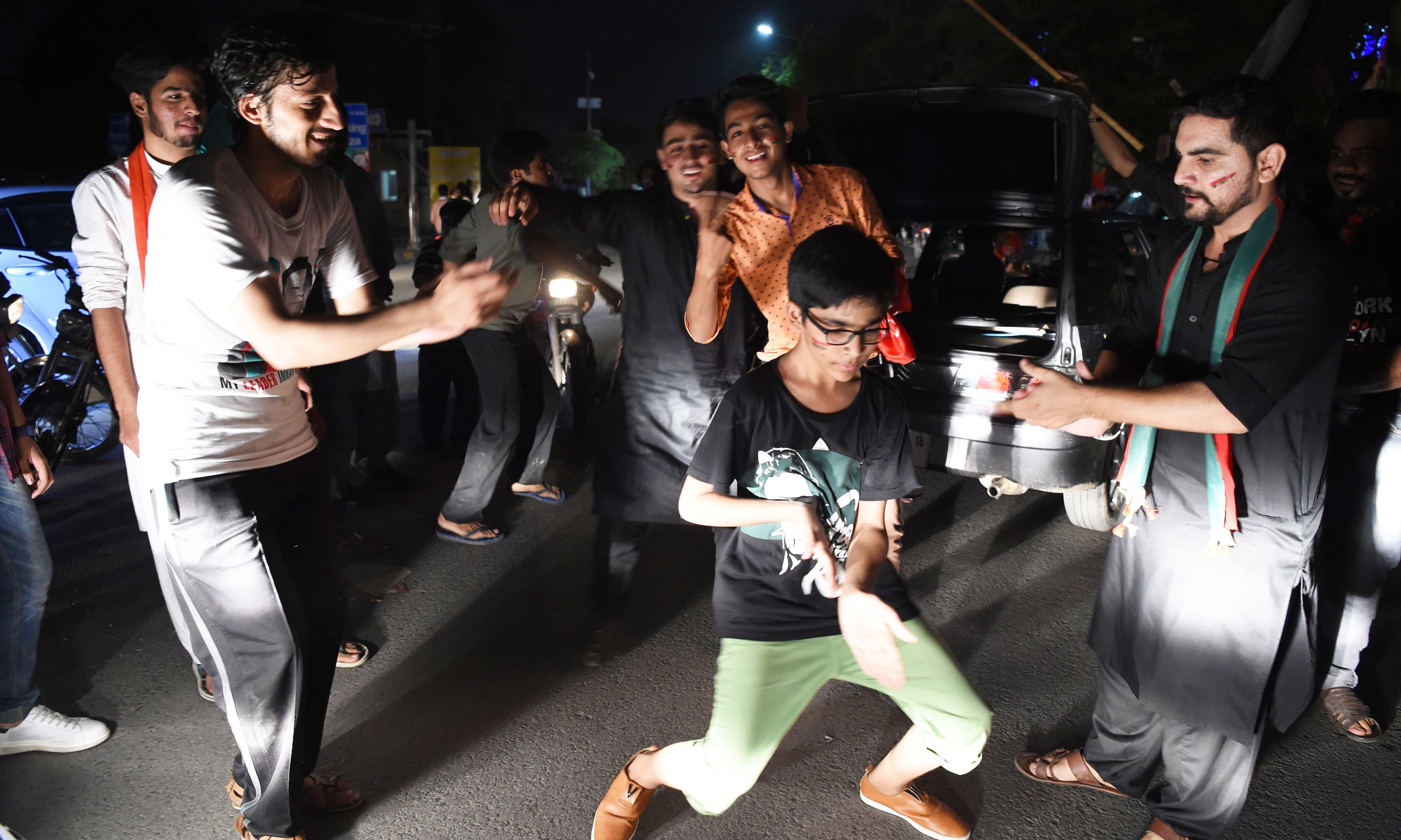 PTI supporters dance as they celebrate in Lahore. —AFP