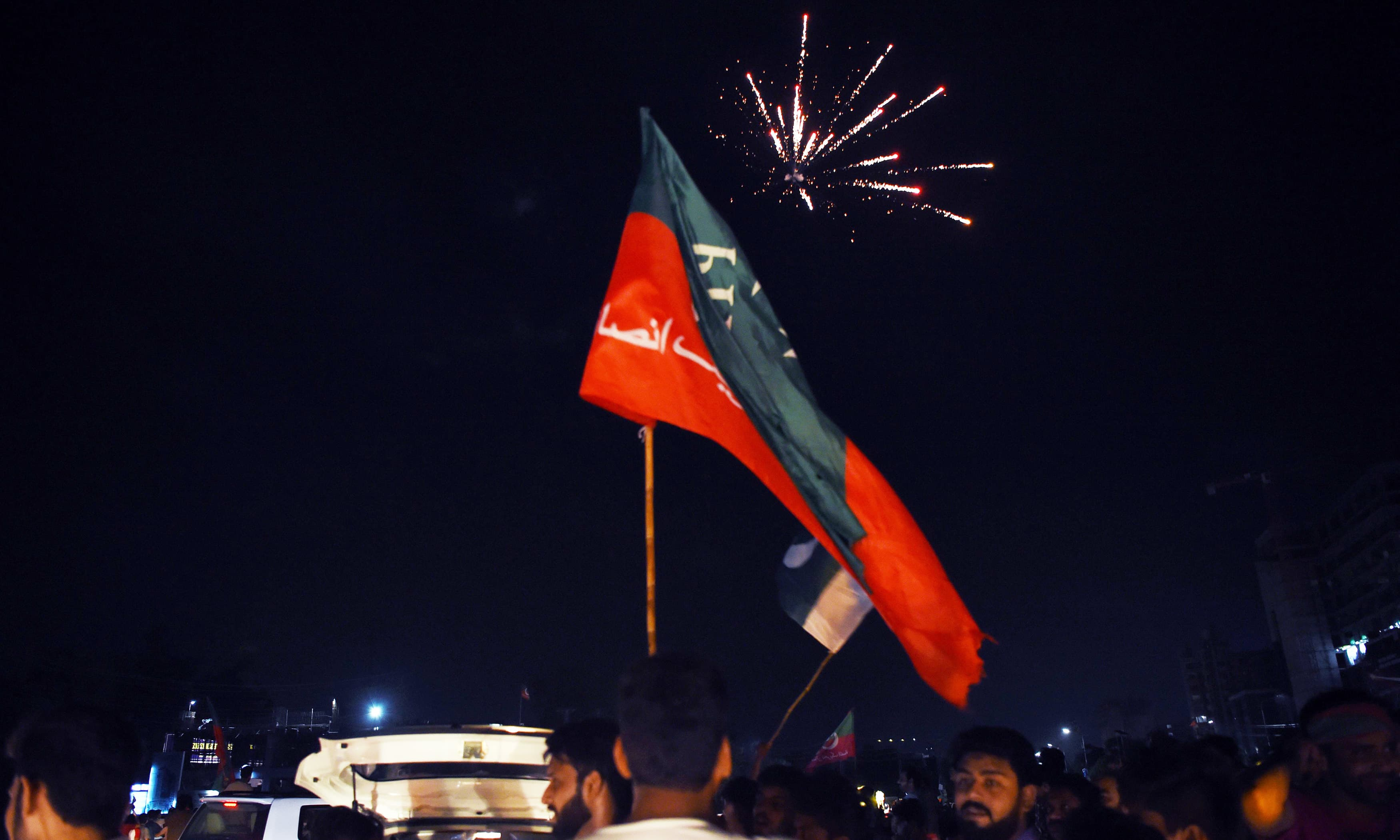 PTI supporters cheer as fireworks go off as they celebrate in Lahore. —AFP