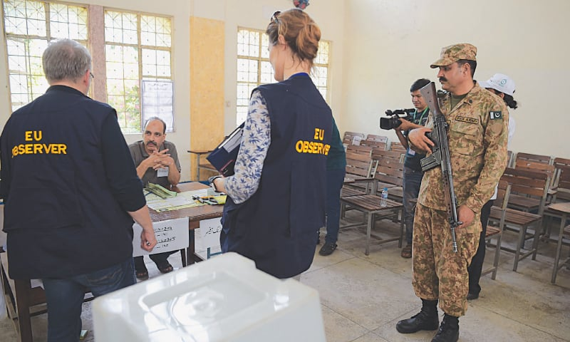 "ISLAMABAD: European Union election observers speak to officials during their visit to a polling station on Wednesday. The European Union's Ambassador to Pakistan, Jean Fracois Cautain, tweeted: ""Already observed with my colleague Elisa a good number of polling stations both in rural and urban Punjab.""—AFP"