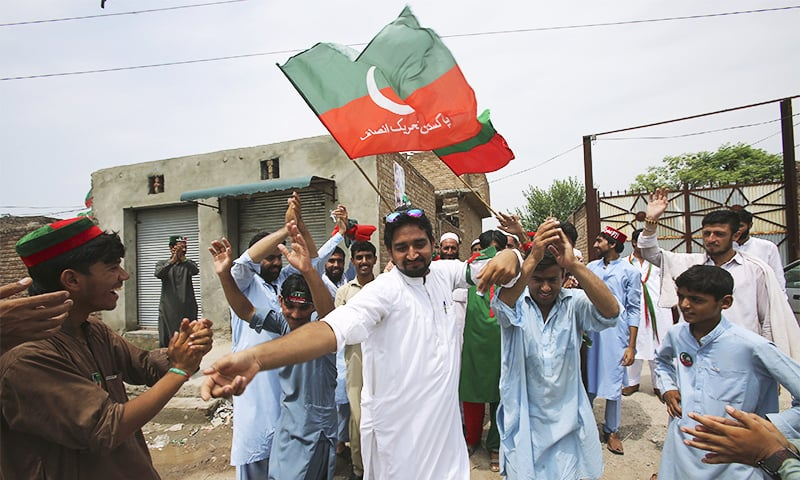 PTI supporters dance to celebrate the victory of their party's candidate in Peshawar. ─ AP