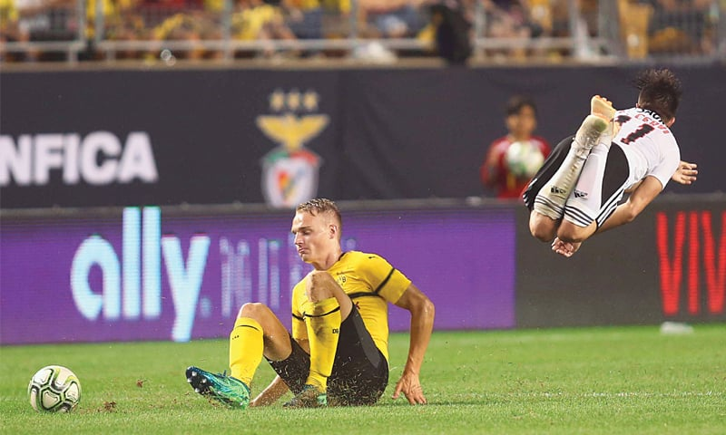 PITTSBURGH (Pennsylvania): Benfica Franco Cervi goes airborne after a slide tackle by Borussia Dortmund's defender Amos Pieper at Heinz Field.—Reuters