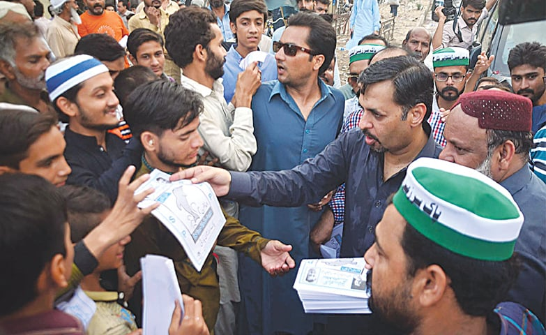 Pak Sarzameen Party chairman Mustafa Kamal distributing pamphlets during his election campaign in Hyderabad.—APP