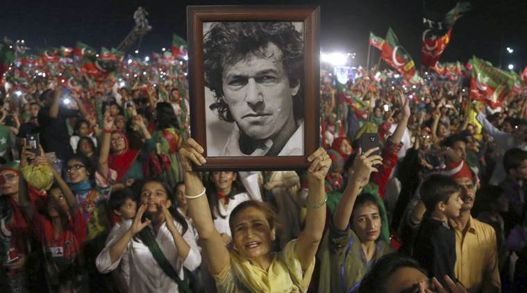 In this July 22 photo, a PTI supporter raises a picture of Imran Khan during an election campaign rally in Karachi. ─ File