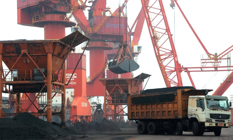 Imported coal is seen lifted by cranes from a coal cargo ship onto a truck at a port in Lianyungang, Jiangsu province on Thursday. —Reuters